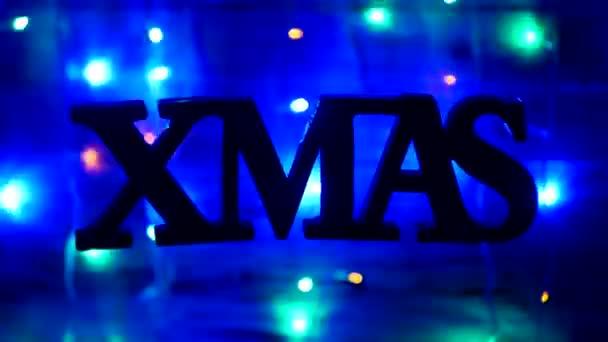Karácsonyi felirat Xmas szabadon fülönfüggők a levegőben, egy fából készült háttér, év új fényeket, újévi ünnepek, szilveszteri 2019, karácsonyi, dekoráció