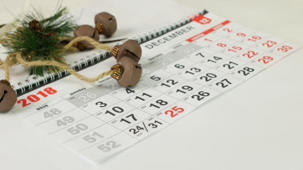 Az asztalon egy naptár kézzel, ceruzával jelek száma 25 ünnep karácsony, közelkép, újévi ünnepek, piros naptári nap, karácsony, ünnepli