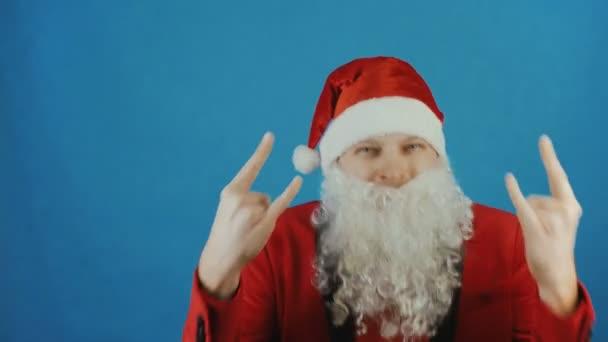 Karácsonyi és újévi, ember, mint a Santa Claus egy szarv, jeleit mutatja-e a kék háttér