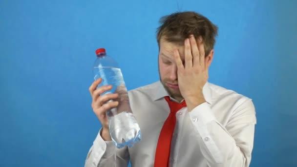 Ein junger kaukasischer Mann mit einem Bart und einen Kater passt eine kalte Flasche Wasser auf seinem Kopf, Kopfschmerzen, Kater, blauer Hintergrund