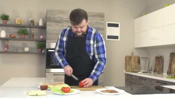 Ein männlicher Koch in einer Schürze schneidet in der Küche eine Tomate, auf dem Tisch liegen die Zutaten für einen Burger, Slow Food.