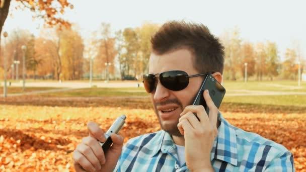 Aerosol vapor exhaled by an e-cigarette stylish bearded caucasian man wearing shirt
