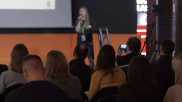 female CEO or speaker tells something during conference or business lecture