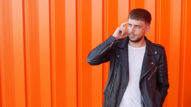 A young caucasian guy with a beard and a pensive face is standing and thinking, orange background, copy space, slow-mo