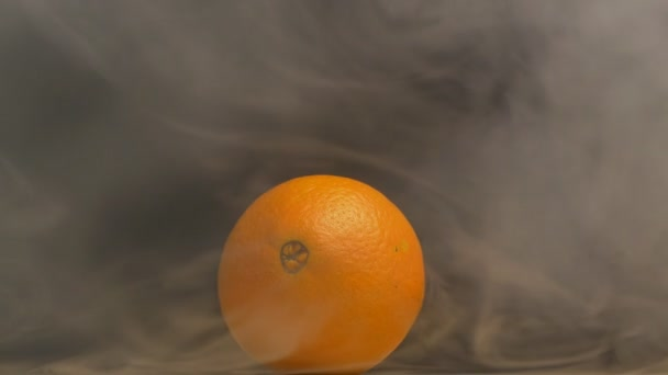 Juicy and ripe orange fruit from which evaporation and freshness are on a black background, close-up, copy space, slow motion