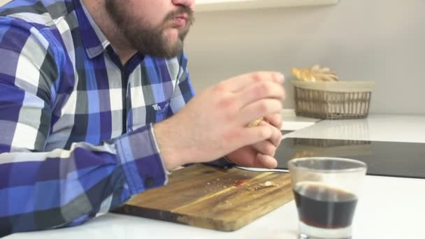 dicker Mann mit Bart im karierten Hemd isst Fast-Food-Cheeseburger und wäscht sich mit schädlicher Limonade, Extrakalorien, Junk Food, Slow-mo, Hintergrund