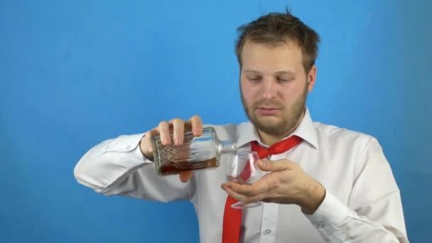 Részeg ember alkoholos, szakáll, egy fehér ing-nyakkendő önti alkohol brandy egy üveg egy pohár és italok, másnaposság