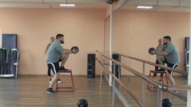 Personal training from athletic girl for fatboy with big abdomen in sportswear. Fat man training with woman instructor and doing exercises in fitness center. Thick obese guy together with personal