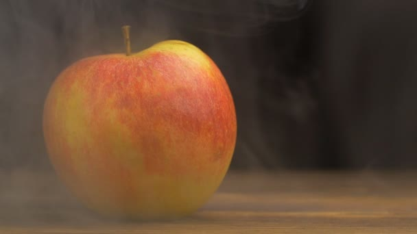 Natural juicy apple from which blows cool and fresh in the smoke on a black background, close-up, copy space, slow motion