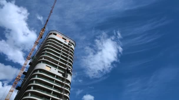 Construction of a high-rise house, work of construction crane, real estate market
