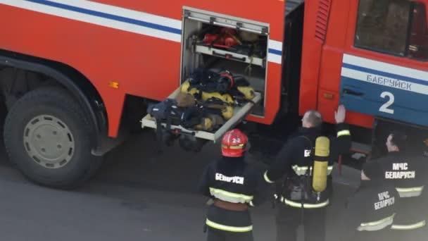 Hasiči uspořádat uniformy a vybavení po hašení ohně v hasičské auto, Bobruisk, Bělorusko 21.02.19
