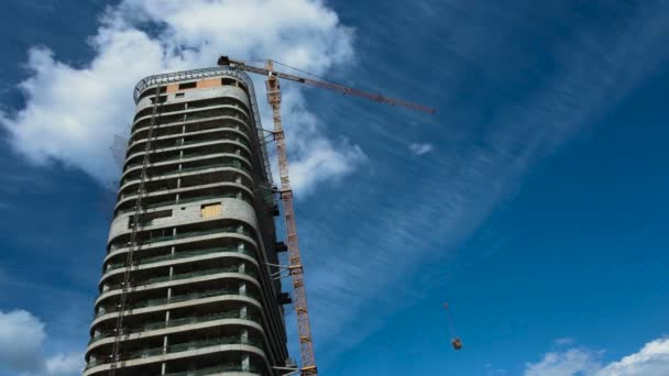 unfinished residential building under blue sky and clouds, construction crane work, copy space
