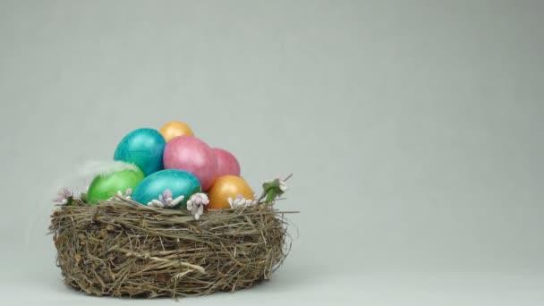 Barevné Kuřecí vejce v hnízdě na bílém pozadí, do něhož spadá lehké pírko, Velikonoce, kopie prostor, Zpomalený pohyb, tradiční