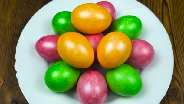 Ruka klade na talíři velikonoční zdobené a malované barevné vejce během neděle vzkříšení nebo Pascha