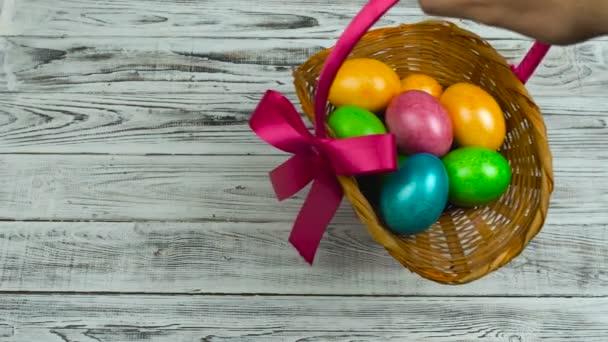 Ruka klade velikonoční košík s barvené a malované vejce na tabulky, pojmu křesťanský svátek Vzkříšení neděli nebo Pascha
