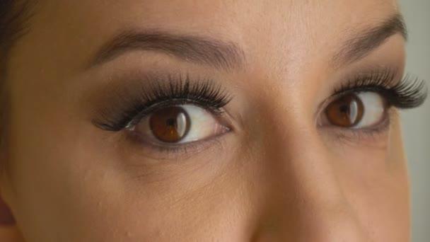 Ženská tvář s hnědýma očima a dlouhé umělé řasy se dívá na kameru. Hezká dívka model s módní make-up