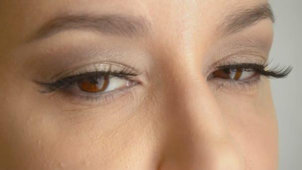 Zenske tvář s dlouhou umělé řasy otevře její hnědé oči a dívá na kamery. Closeup hezký ženský model s roztomilý make-up