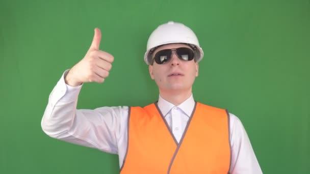 der Chef in schwarzer Brille am Arbeitsplatz gibt dem Kranführer den Befehl, die Last hochzuheben, grüner Hintergrund, hromakey, Schleuder