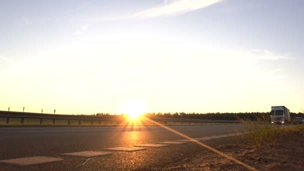 Moderní nákladní vůz transportuje náklad na pozadí západu slunce. Koncepce řidičů nákladních automobilů v oblasti nákladní a logistické, kopírovací prostory, komerční