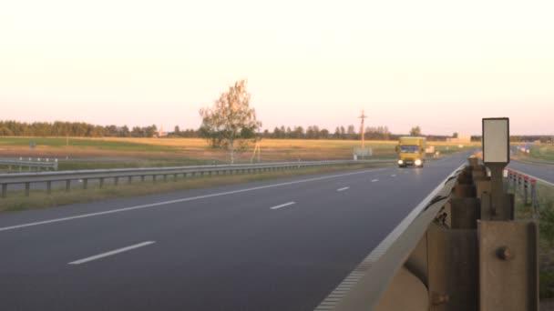 Il moderno carrocarri trasporta il carico sullo sfondo di un tramonto. Il concetto di camionisti nel campo del trasporto merci e logistica, spazio di copia,