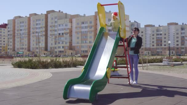 Kavkazská matka a její hravé dcerka hrají na barevném, novém a moderním hřišti, jezdí po kopci