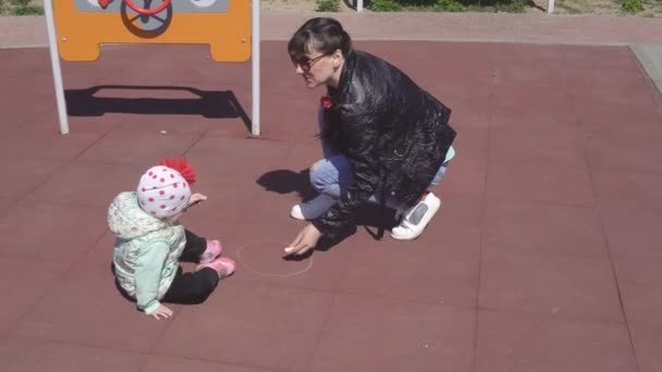 Beautiful caucasian mother draws with crayons with her little daughter 3 years old on the playground