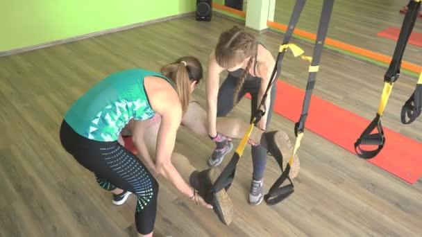 zwei schöne kaukasische Mädchen Trainer helfen einem dicken Mann, eine Übung in der Turnhalle auf Scharnieren trx zu tun