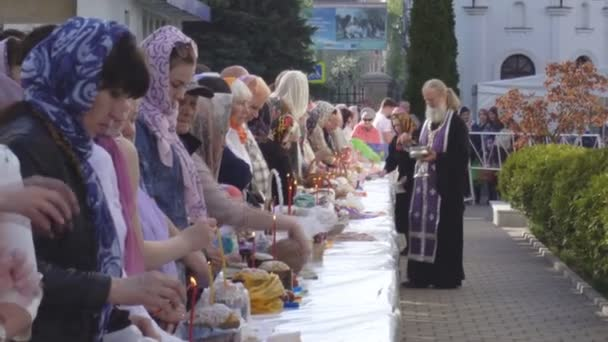 Church holiday Easter, consecration of Easter cakes and eggs in the church, tradition, clergyman BOBRUISK, BELARUS - April 27, 2019