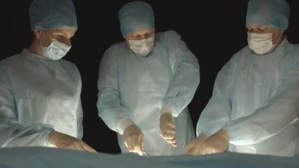 Tři chirurgové, muž a žena, provádějí chirurgii v operačním sále, aby odstranili a transplantaci lidských orgánů, resetli žaludek a odstranili žlučník, přívěšek