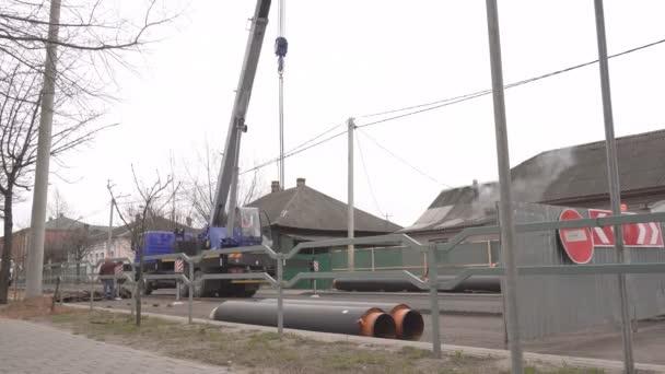 Ve městě pracuje na výměně a demontáži trubek pro vytápění, jeřáb vleže nové trubky pro pokládání pod silnici, městská infrastruktura