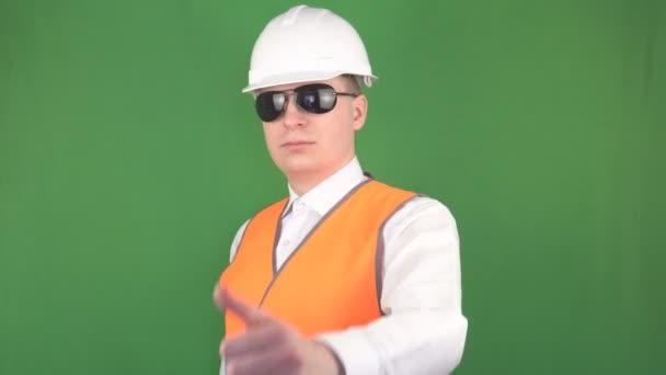 ein Mann mit schwarzer Brille und weißem Schutzhelm zeigt den Daumen in die Kamera, alles ist in Ordnung, grüner Hintergrund, hromakey