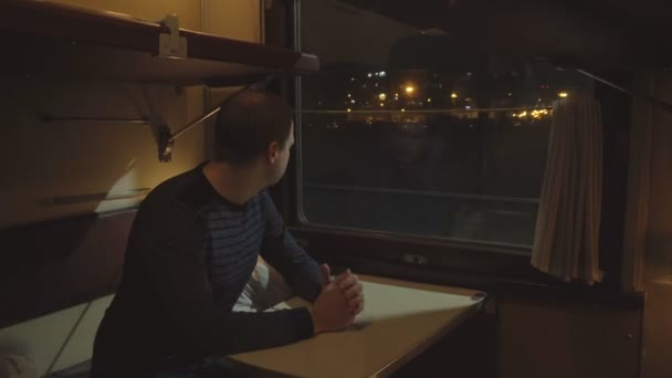A male passenger rides in a compartment car of a railway train and looks out the window, traveling by rail, night