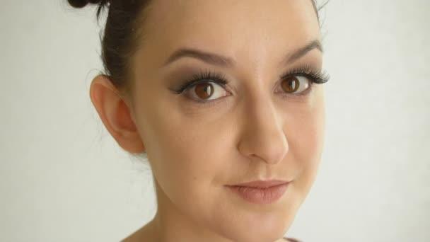 Női arc hosszú hamis szempillák és barna szeme néz kamera. Closeup gyönyörű lány modell csinos smink fehér háttér