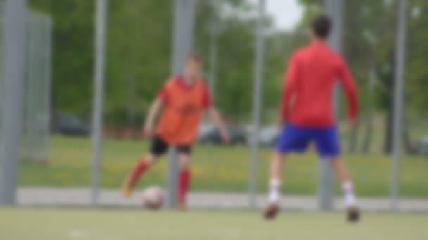 Kluci hrají fotbal na stadionu, ten chlap dělá ostrej a kope s míčkem, pozadí, kopírovací prostor, pomalý pohyb, rozmazaný