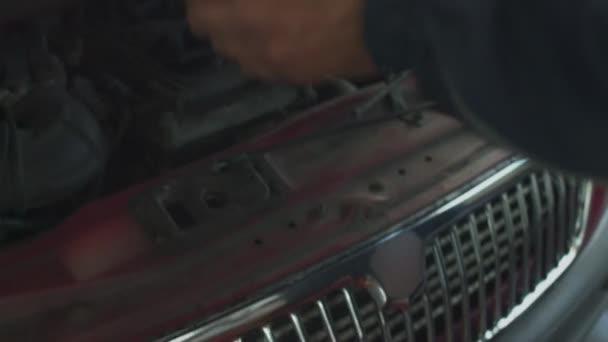 Muž otevírá kapotu auta u servisního stanoviště a technickou prohlídku diagnostiky