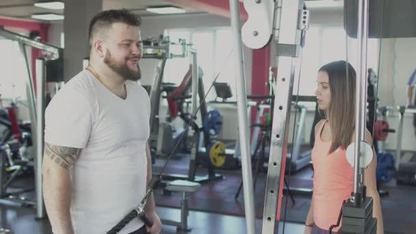 Tlustý obézní chlapík s individuálním trenérem dělá v tělocvičně nějaké fyzické trny. Nadváha muž a ženský trenažér spalí kalorie. Buclatý samec s osobním instruktorem pro fitness cvičení. Soukromé vzdělávání