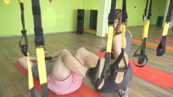 schöne Mädchen Trainer hilft, auf einem klappbaren trx bärtigen dicken Mann zu üben, Krafttraining
