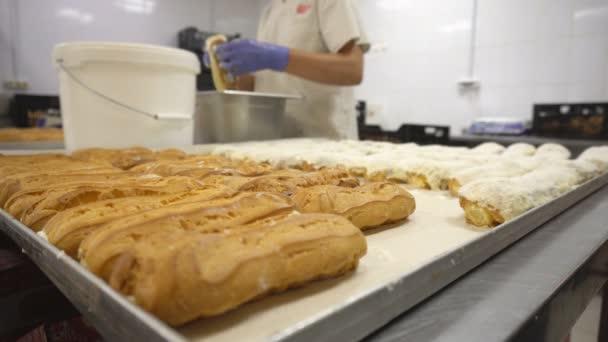 Cukrásza borítók eclairs a mázzal vagy csokoládé jegesedés. Az édes bagett desszertek manuális gyártása. Sütőipari termékek. Malomipari termékek.