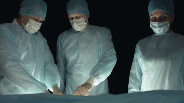 Ein Chirurgenteam operiert einen Patienten während des Eingriffs. Arzt mit Skalpell und Pinzette schneidet Patienten Gewebe. Assistenten helfen bei Operationen im Krankenhaus. Krankenschwester tränkt Blut mit Wattestäbchen.