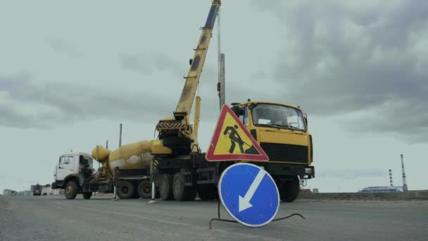 Arbeiter installieren entlang der Straße einen Mast mit Straßenbeleuchtung per Autokran. Baumaschinen, Beton- oder Zementmischer-Transportwagen sind im Einsatz. Ingenieure stellen Laternenpfahl auf Autobahn auf