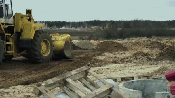 Strojírenský víceúčelový stroj nebo jednonákladový kolový traktor s lopatkami na staveništi k provádění nakládacích a vykládacích prací s půdou během fáze výstavby silnic