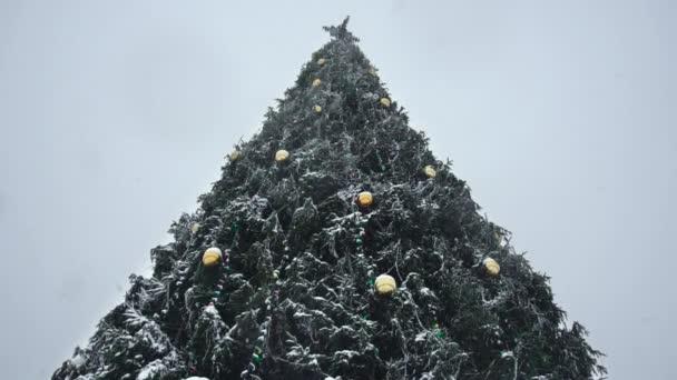 Lényegében a díszített karácsonyfa hóesésben. Szilveszter a hóviharban a városban. Tél. Fogalom a kezdete ünnepek és ünnepségek hóvihar vagy szélvihar. Rossz idő lassított felvételen