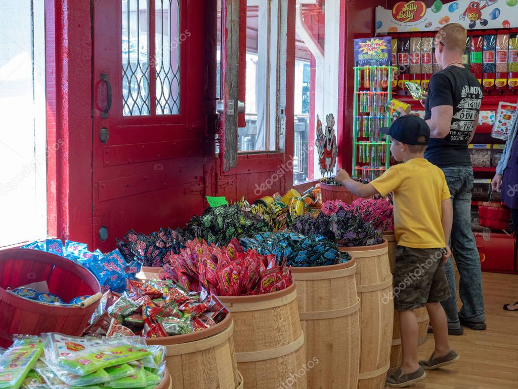 A young boy and his father dig through various bins at a candy store
