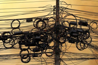 High-voltage power cord, wire tangle electrical energy on sky background evening atmosphere