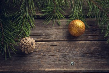 Yellow Christmas ball and pine cone with pine or fir branch on old worn wooden surface