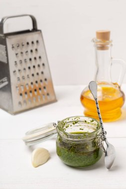 Jar with basil pesto sauce on table