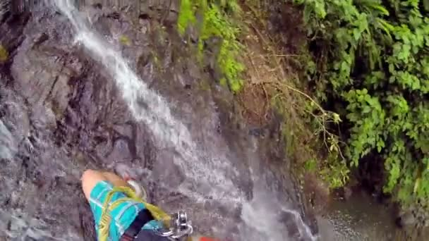 Man Looking down below the High Amazing Waterfalls while Rappelling