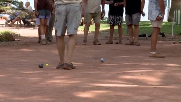 Zoom-in: sportovní muži náročné navzájem míčové hry zvané p? tanque ve stínu v Azurovém pobřeží ve Francii
