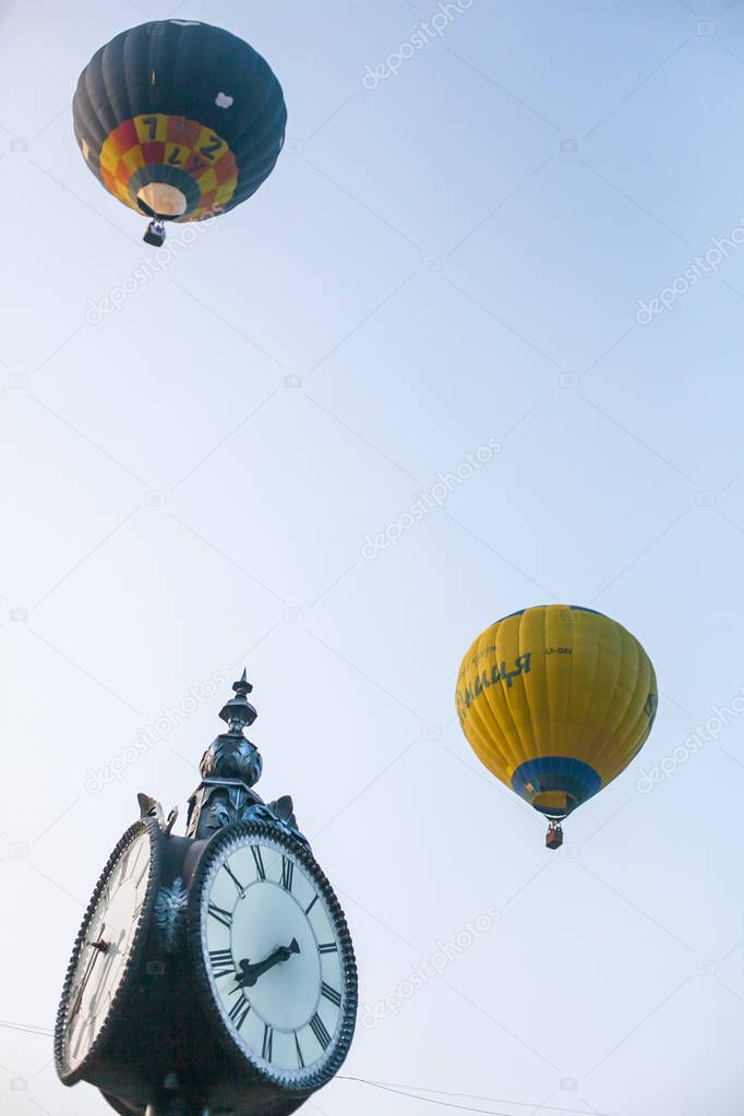 hot air balloon in flight and old clock on blue sky