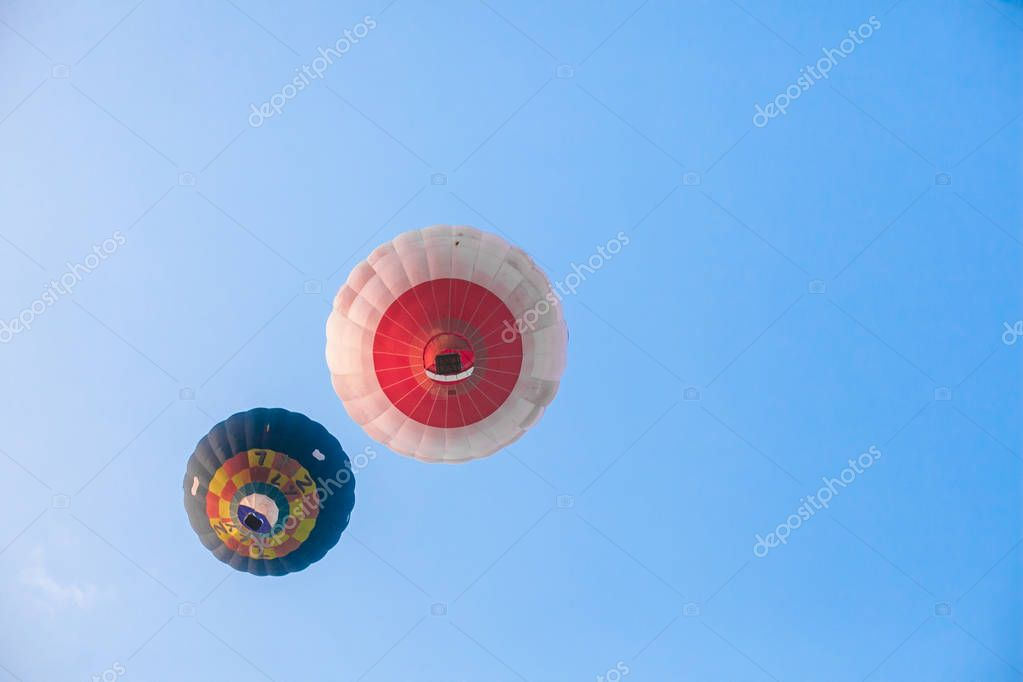 two hot air balloons in flight on blue sky